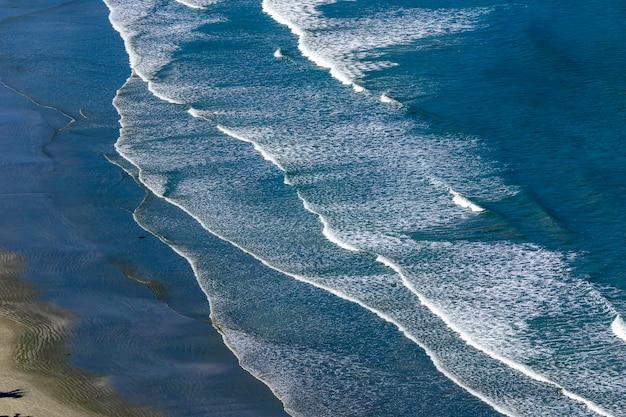 Fale rozbijające się na plaży z błękitnym morzem na północnym wybrzeżu sao paulo. sao sebastiao, sp, brazylia