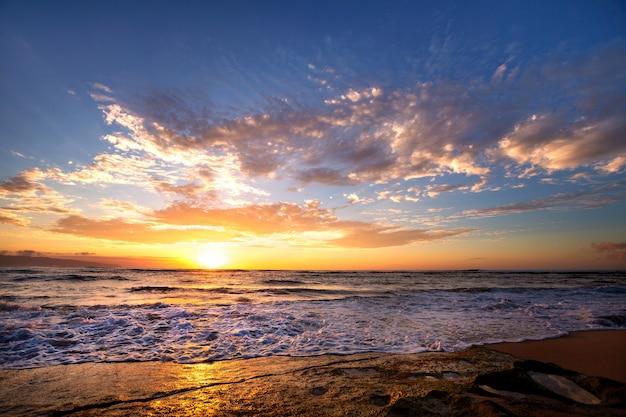 Fale rozbijające się o skały po zachodzie słońca w pobliżu sunset beach, oahu, hawaje