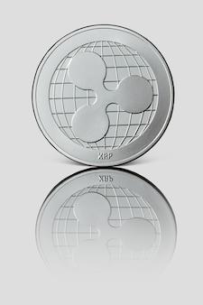 Fale srebrnej monety. awers monety odbija się na białej błyszczącej powierzchni. światowa kryptowaluta