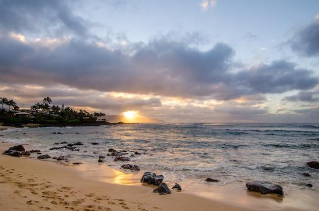Fale toczą się nad małymi koralowymi skałami przy chun rafą i jocko zatoczką na oahu, hawaje przy