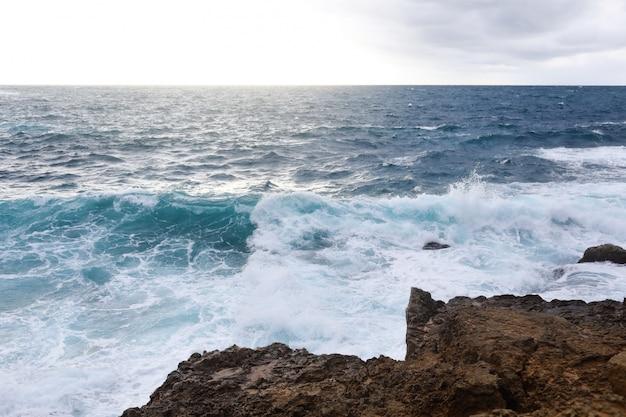 Fale uderzające w skaliste klify na plaży na cyprze. ta pogoda może być niebezpieczna dla sportów wodnych, ale jednocześnie fale i ich rozpryski są ładne i dzikie