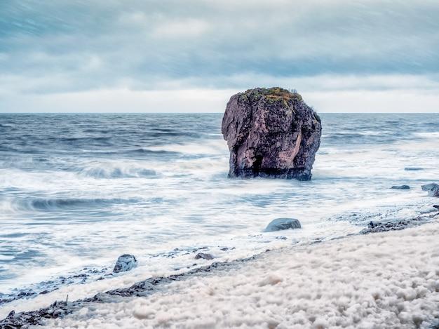 Fale z białą pianą toczą się po skalistym brzegu.