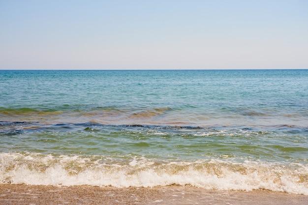 Fale z pianką na wybrzeżu morza egejskiego w grecji na krecie.