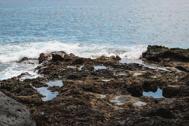 Falista woda długiego strzału na skalistym brzegu