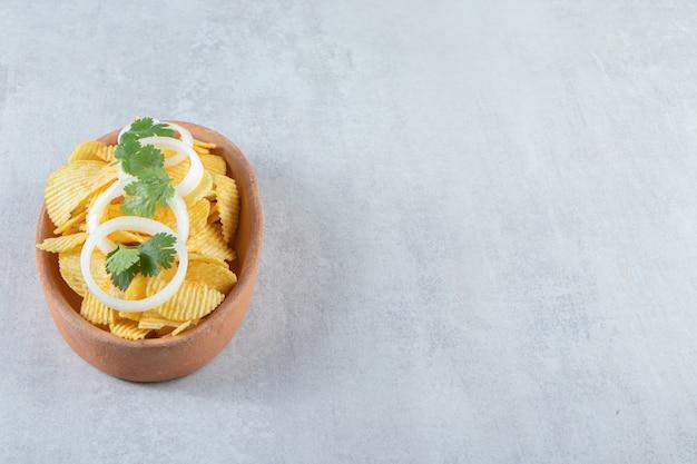 Faliste chipsy ozdobione krążkami cebuli w ceramicznym talerzu.
