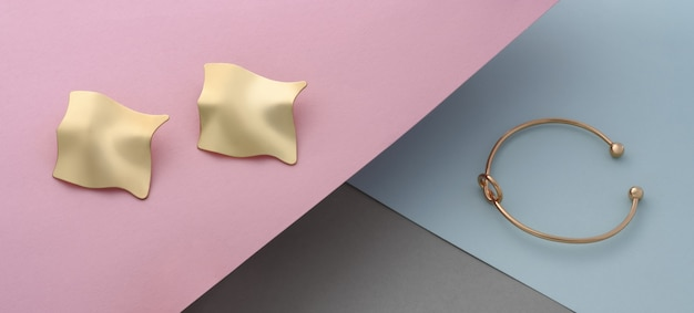 Faliste kolczyki w kształcie pary i bransoletki w kształcie węzła na tle papieru w pastelowych kolorach
