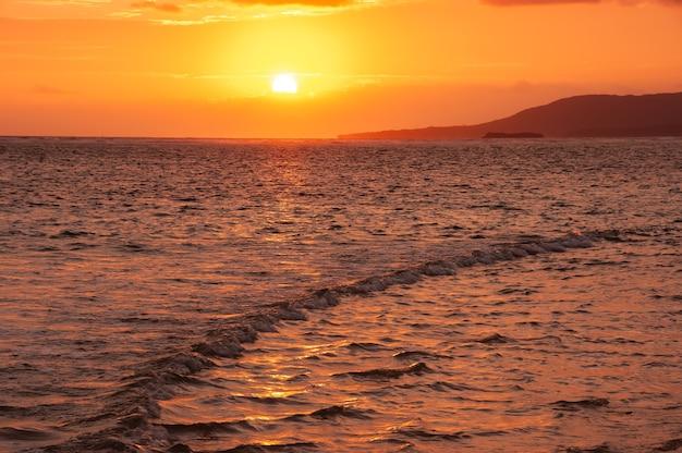 Faliste ruchy promieniującego wschodu słońca płynące nad morską wyspą iriomote
