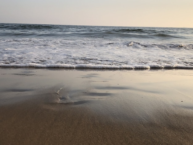 Falisty ocean uderzający w piaszczystą plażę i lśniący pod kolorowym niebem