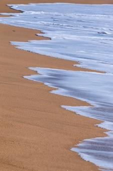 Falowa tekstura na plażowym piasku
