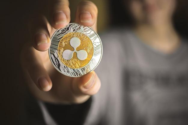 Falowanie monety w dłoni młodej kobiety, zbliżenie kryptowaluty, zdjęcie tła biznesowego