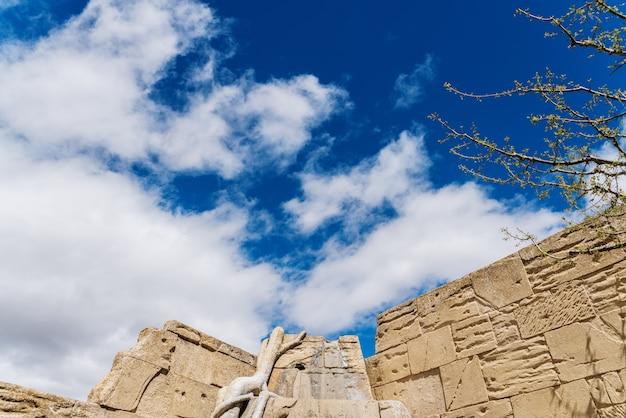 Fałszywe kamienne ściany pokryte winoroślą roślinności i błękitne niebo z chmurami