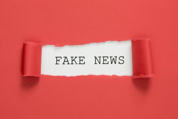 Fałszywe słowa wiadomości rozdarte na czerwonym papierze