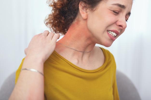 Fałszywe srebro. młoda klientka cierpiąca na bolesność skóry wyglądająca na zakłopotaną noszeniem nowo zakupionego fałszywego srebrnego naszyjnika, powodującego reakcję alergiczną jej ciała w postaci wysypki