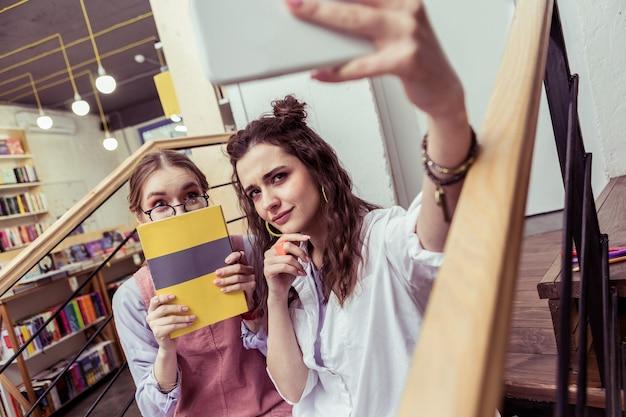 Fałszywy obraz. zadowolone młode damy fotografujące się i pozujące z książką oraz z uroczymi twarzami