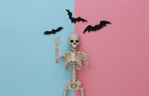 Fałszywy szkielet i nietoperze na różowym niebieskim pastelu. halloweenowa dekoracja, przerażający motyw