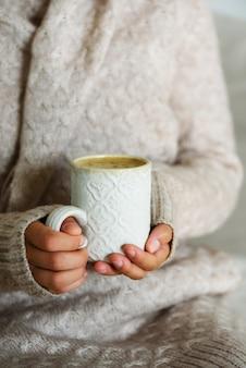 Famale trzyma w dłoni przytulny ceramiczny kubek z kawą. koncepcja czasu zimowego i świątecznego domu. styl życia.