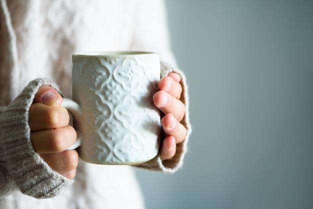 Famale trzyma w dłoni przytulny ceramiczny kubek z kawą. koncepcja czasu zimowego i świątecznego domu.