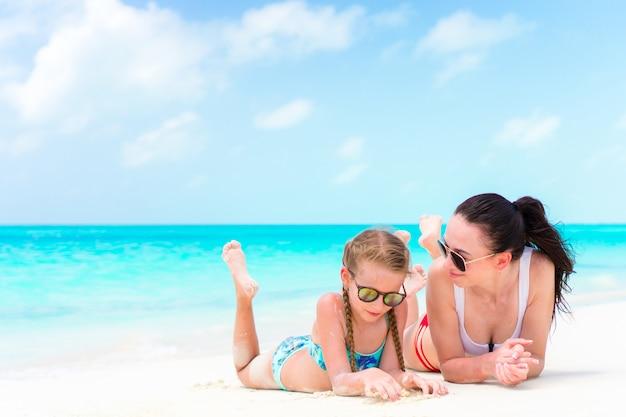 Familly na tropikalnej plaży. mama i dziecko cieszą się wakacjami