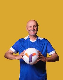 Fan piłki nożnej mężczyzna trzyma piłkę w dłoniach w zacisznej ścianie