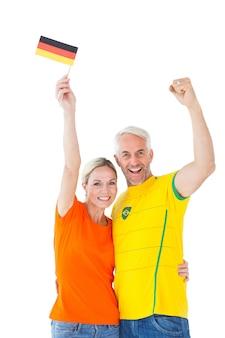 Fan piłki nożnej pary doping i ono uśmiecha się przy kamerą