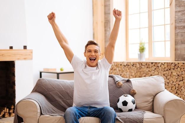 Fan piłki nożnej. przystojny, zachwycony, dobrze zbudowany nastolatek, uśmiechnięty i unoszący ramiona, siedzący na kanapie i piłka nożna obok niego