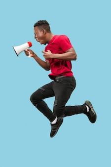 Fan piłki nożnej skoki na pomarańczowym tle. młody człowiek afryki jako fan piłki nożnej z megafonem na białym tle na niebieskim studio. koncepcja wsparcia. ludzkie emocje, koncepcje wyrazu twarzy.