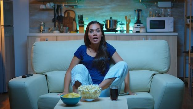 Fan sportu ogląda ulubioną drużynę siedzącą na kanapie w życiu wspierając i krzycząc w telewizji na zawodach piłki nożnej. podekscytowana, sama w domu pani w piżamie ciesząca się wieczorem przed telewizorem.