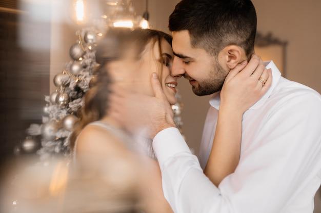 Fancy ubrany mężczyzna i kobieta w srebrnej sukni przytulić siebie przetargu stojący przed choinką