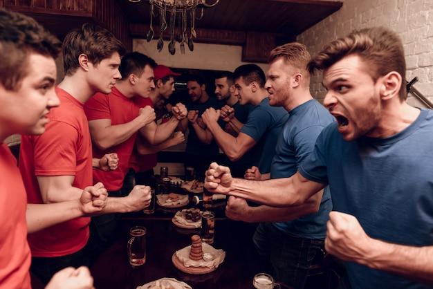 Fani czerwonego zespołu i fani niebieskiej drużyny walczą.