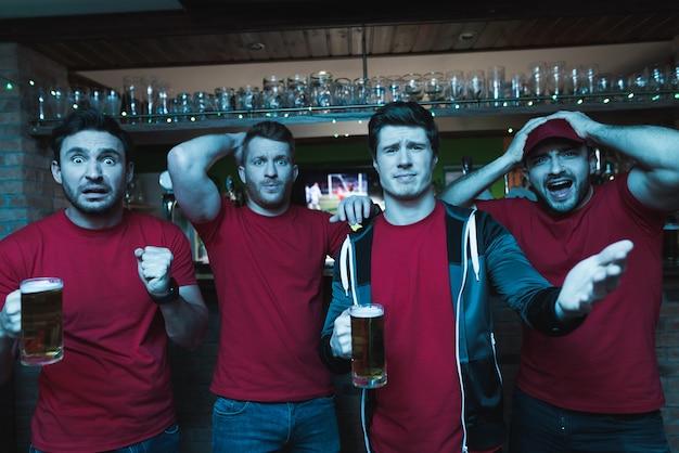 Fani krzyczący smutno przed telewizorem piją piwo.