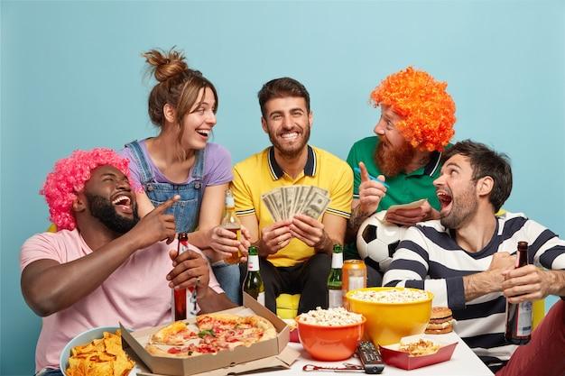 Fani piłki nożnej, koncepcja szczęścia i zabawy. rozradowany przyjaciel zadowolony z sukcesu w zakładzie piłkarskim, wygrać ryczałtową sumę pieniędzy, trzymać dolary, jeść smaczną przekąskę, siedzieć przy stole, śmiać się głośno, odizolowany na niebiesko