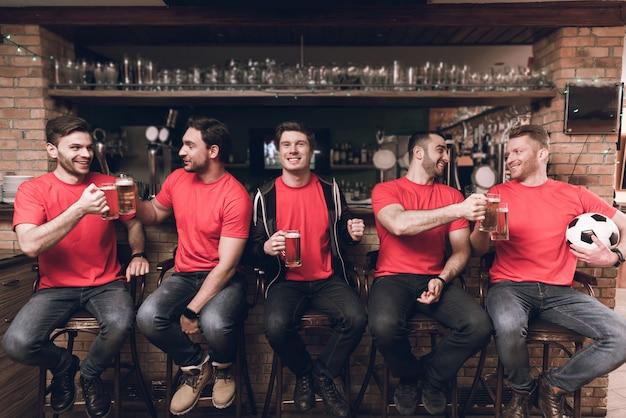 Fani piłki nożnej oglądają grę pijącą piwo.