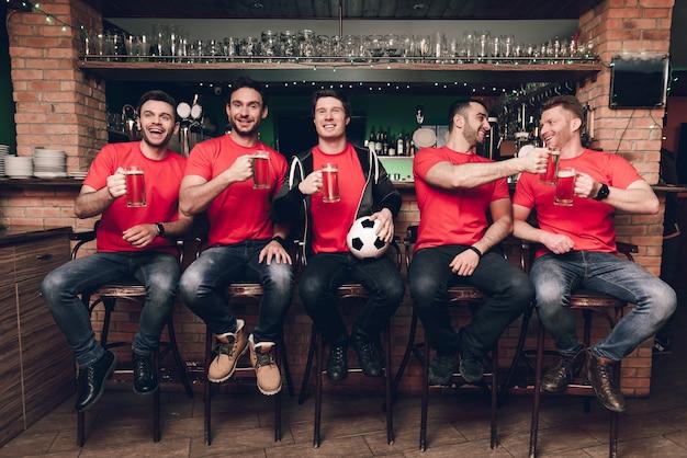 Fani piłki nożnej oglądają grę pijącą piwo