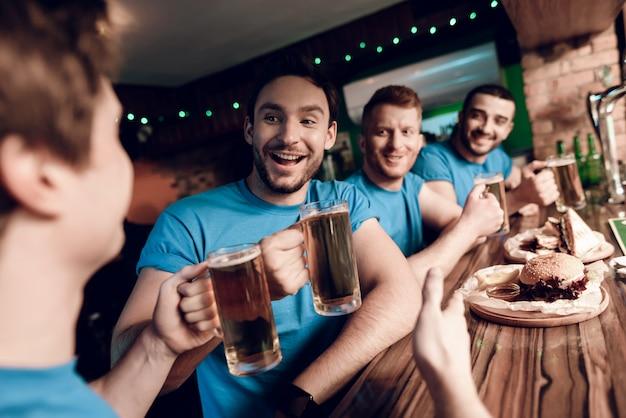 Fani piłki nożnej oglądają grę z piwem i jedzą.