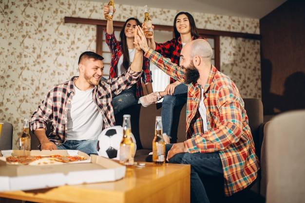 Fani piłki nożnej oglądający programy telewizyjne w domu, przyjaciele szczęśliwi ze zwycięstwa.