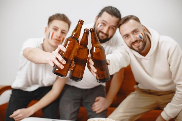 Fani piłki nożnej siedzą na kanapie w salonie i piją piwo