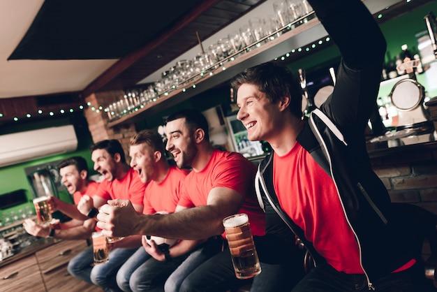 Fani piłki nożnej świętujący i dopingujący picie piwa