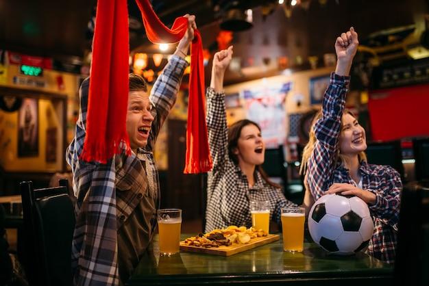 Fani piłki nożnej w szalikach oglądają mecz i podnoszą ręce w barze sportowym. transmisje telewizyjne, młodzi przyjaciele odpoczywają w pubie, ulubiona drużyna wygrywa