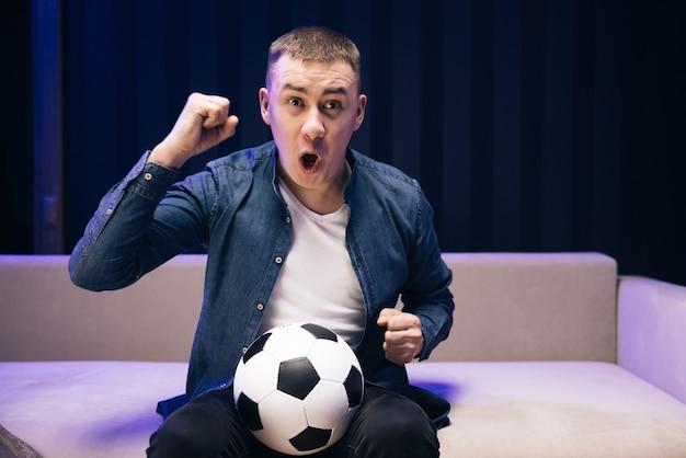 Fani piłki nożnej zabawnego faceta kibicują wspierając ulubioną drużynę trzymającą piłkę nożną