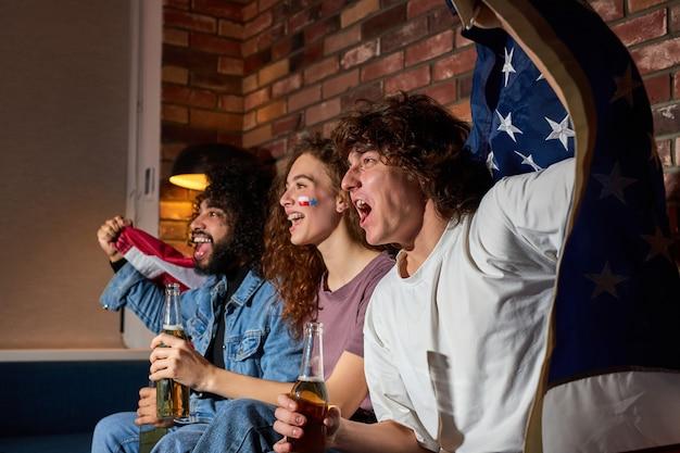 Fani różnych sportów świętują zwycięstwo w domu. namiętni kibice krzyczą oglądając mecz w telewizji, wiwatując razem, krzycząc emocjonalnie