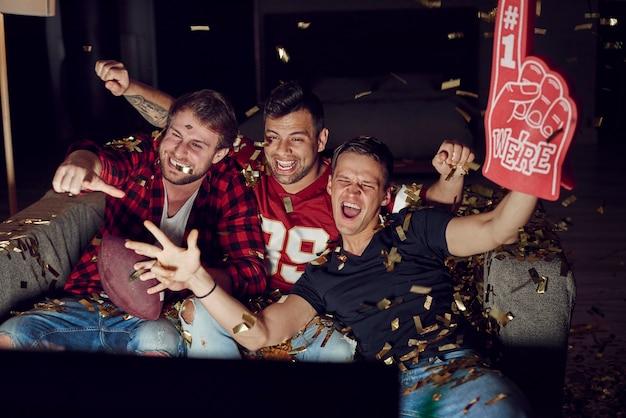Fani sportu dopingują wśród spadających konfettietti