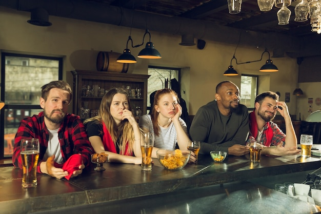 Fani sportu kibicują w barze, pubie i piją piwo podczas mistrzostw, rywalizacja trwa