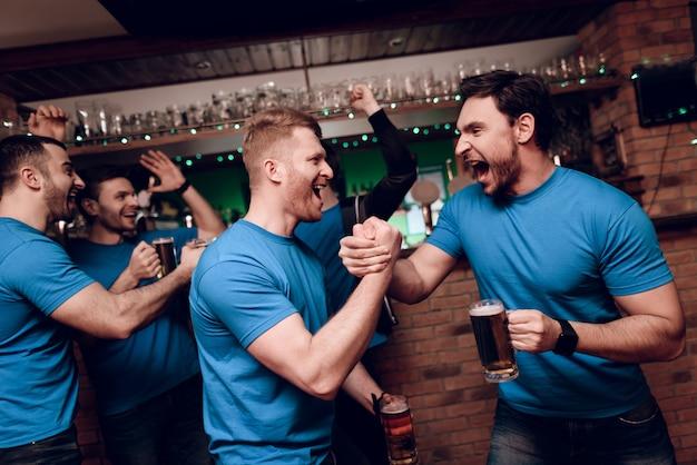Fani sportu pijący niedźwiedzia dopingującego na barze sportowym.