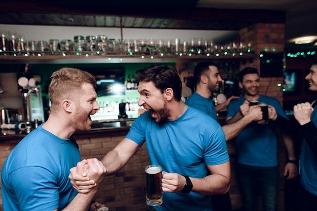 Fani sportu pijący niedźwiedzia dopingującego na barze sportowym