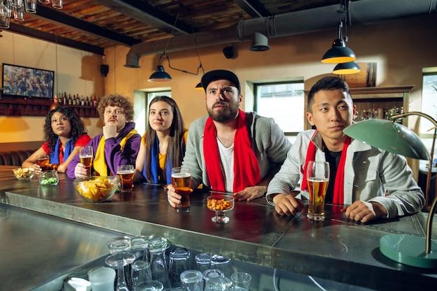 Fani sportu wiwatujący w barze, pubie i pijący piwo podczas mistrzostw, rywalizacja trwa. wieloetniczna grupa przyjaciół podekscytowana oglądaniem tłumaczenia. ludzkie emocje, ekspresja, koncepcja wspierająca.