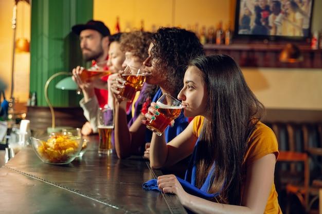 Fani sportu wiwatujący w barze, pubie i pijący piwo podczas mistrzostw, rywalizacja trwa. wieloetniczna grupa przyjaciół.