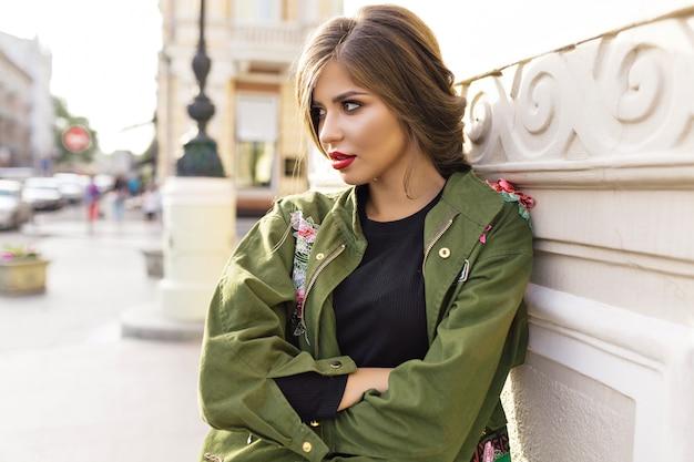 Fantastyczna brunetka ze stylową fryzurą i czerwonymi ustami pozuje na ulicy