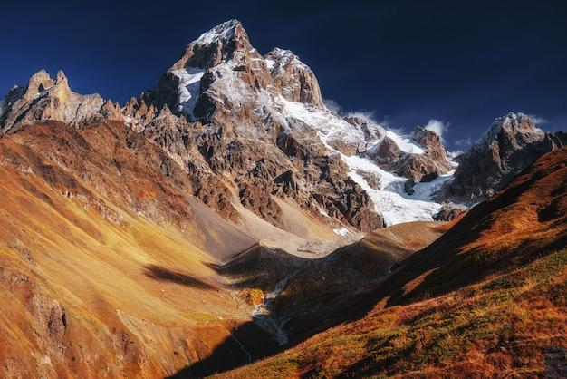 Fantastyczna sceneria i ośnieżone szczyty w pierwszym porannym słońcu.
