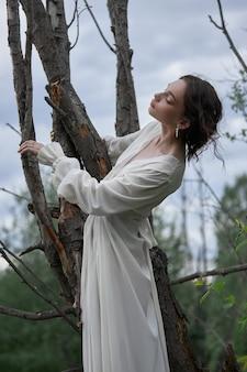 Fantastyczna wróżka piękna kobieta w białej długiej sukni na starym suchym drzewie. księżniczka dziewczyna w bagnie. moda model sexy dziewczyna pozuje na drzewie nad jeziorem. bajka