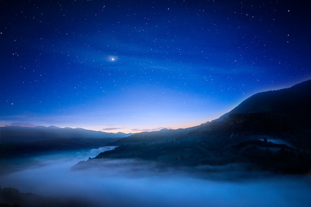 Fantastyczne nocne niebo nad górami.